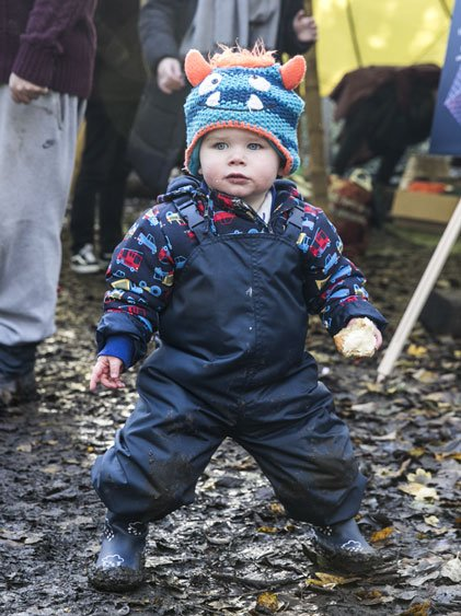 little boy playing in Grass & Air navy stomper slacks and colour-changing wellies at Mud Fest