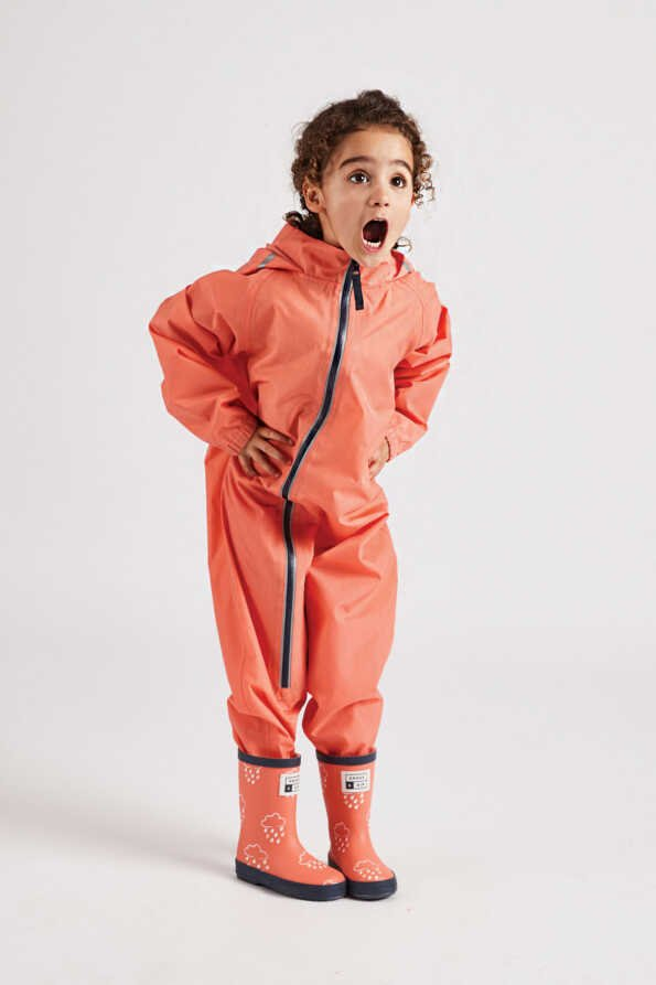 coral puddle suit with contrast navy zip and stirrups: lifestyle front view