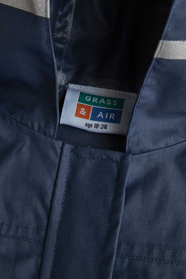 kids navy rain coat label and storm flap detail